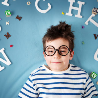 seven years old child lying with glasses and letters on blue background